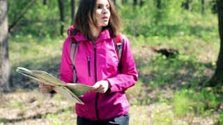 Young  beautiful woman with a map looking for direction in forest