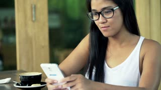 Young beautiful woman with smartphone in cafe