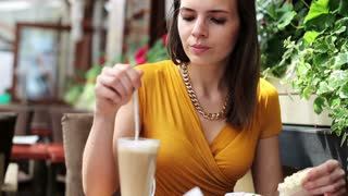 Young, beautiful woman eat and drink sitting in outdoor cafe