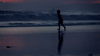 Young boy running into sea during sunset, super slow motion