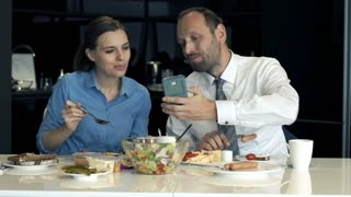 Young business couple sitting with smartphone and talking during breakfast