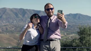 Young business couple taking selfie photo with cellphone on terrace in the country