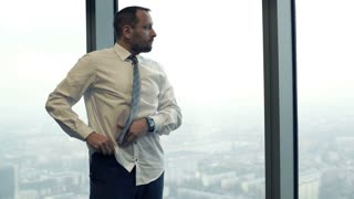 Young businessman dressing up shirt and go away