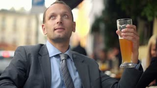 Young businessman drinking cold beer in outdoor bar