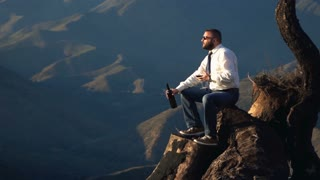 Young businessman drinking wine and admire view sitting on the trunk in the mountains, super slow motion