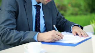young businessman having headache while working with documents in the garden