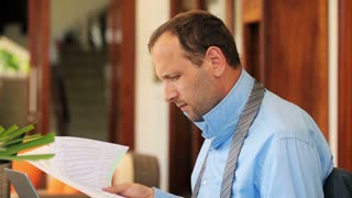 young businessman overwhelmed by documents by table at luxury home