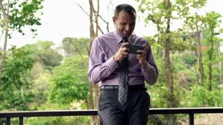 Young businessman playing game on smartphone standing on the terrace