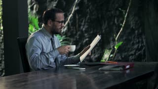Young businessman reading magazine by table at home