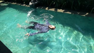 Young businessman swimming in the pool, super slow motion