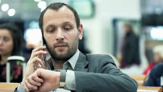 Young businessman talking on cellphone in train station