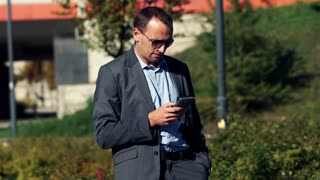 Young businessman texting on smartphone in the city