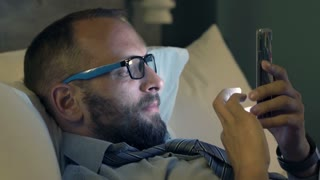Young businessman using smartphone lying on bed at night