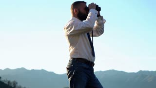 Young businessman with binoculars looking on something in country mountains, super slow motion