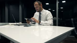 Young businessman with tablet computer sitting by table in the office during night, 4K