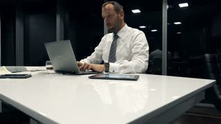 Young businessman working on laptop sitting in office by night, 4K