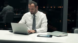 Young businessman working on laptop sitting in office by night