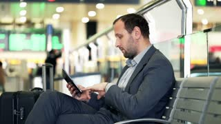 Young businessman working with tablet at train station