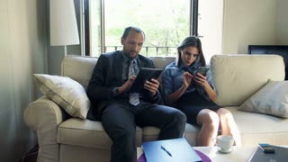 Young businesspeople working with tablet computer and smartphone at home