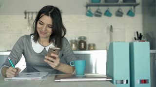 Young businesswoman comparing data on smartphone and documents in the kitchen, 4K
