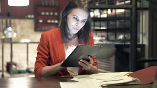 Young businesswoman comparing data on tablet computer and documents by table at kitchen