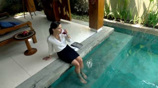 Young businesswoman relaxing with wine by the swimming pool, top view 240fps