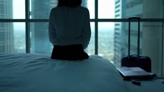 Young businesswoman sitting in the hotel room with splendid view and looking through the window