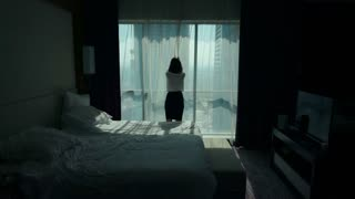 Young businesswoman unveil curtain and looking out of window in the hotel room, super slow motion