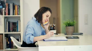 Young businesswoman with documents talking on cellphone sitting at table in home