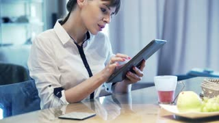 Young businesswoman with tablet computer sitting by table at home
