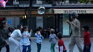 Young children playing soap bubbles with a street entertainer, super slow motion - EDITORIAL