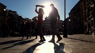 Young couple dancing during sunny day in the city super slow motion