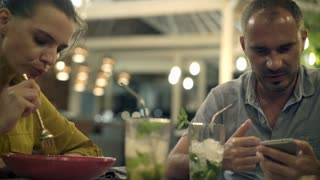Young couple during lunch in cafe, man using smartphone, 4K