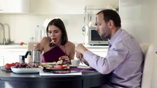 Young couple eating breakfast at home