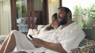 Young couple in bathrobe watching TV while sitting on sofa in outdoor villa