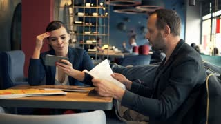 Young couple in cafe, woman using smartphone and man reading newspaper