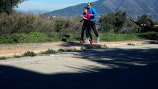 Young couple jogging on sidewalk in the country mountains, 4K