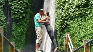 Young couple kissing by beautiful waterfall In Bali, super slow motion, 240Fps
