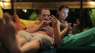 young couple looking at smartphone and tablet late at night