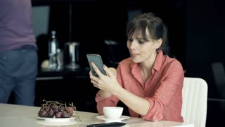 Young couple looking at something funny on smartphone in the kitchen