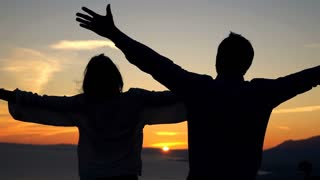 Young couple raising arms to sky standing on the beach during sunset, 240fps