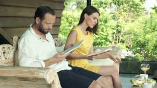 Young couple reading book and magazine on sofa on terrace
