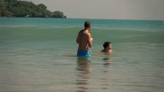 Young couple relaxing in the sea, super slow motion
