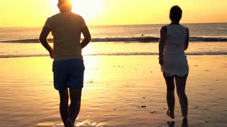 Young couple running and jumping on beach during sunset, slow motion shot at 240fps