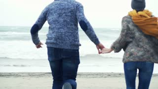 Young couple running to the beach and holding hands on a stormy day, 240fps
