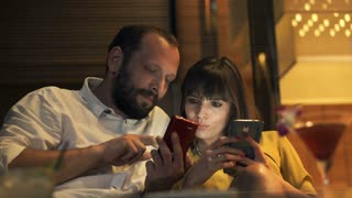 Young couple showing something to each other on smartphone in cafe in the night