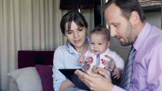 Young couple sitting with her child over tablet on sofa at home