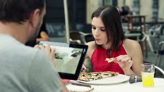 Young couple sitting with smartphone, tablet and eating pizza in cafe