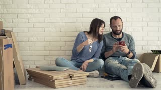 Young couple taking selfie photo with cellphone sitting on floor at their new home