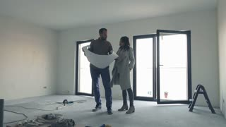 Young couple talking and analyzing blueprints at their new home